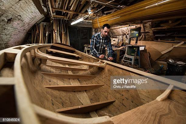 Boat builder Luan Keloposho planes the sides of a row boat project taken on after a previous builder had it in their garage as they could not finish...