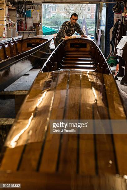 Boat builder Luan Keloposho polishes two racing punts built at the traditional Richmond Bridge Boathouses on the banks of the River Thames on...