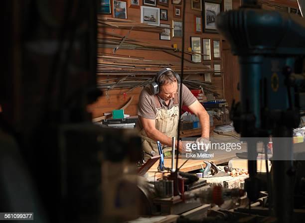 Boat builder sanding wood in workshop
