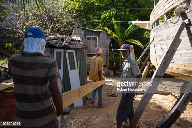 WINDWARD CARRIACOU GRENADA FEBRUARY 6 Boat builders Ricky Patrice left and Curtis St Hilaire center carry a tapered plank made of pitch pine wood to...
