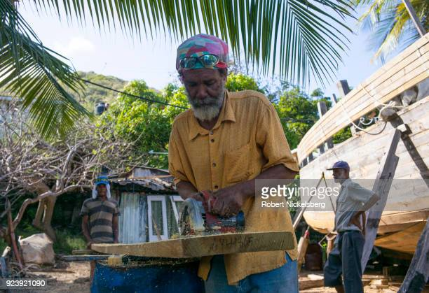 WINDWARD CARRIACOU GRENADA FEBRUARY 6 Boat builders Ricky Patrice left and Curtis St Hilaire center cut a tapered plank made of pitch pine wood to...