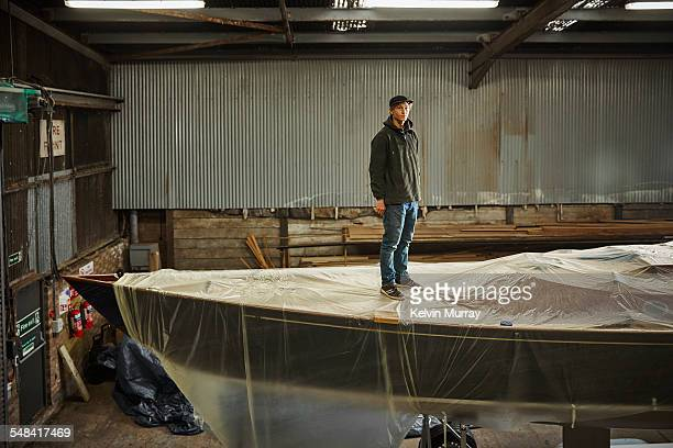 boat building craftsmen - green coat stock pictures, royalty-free photos & images