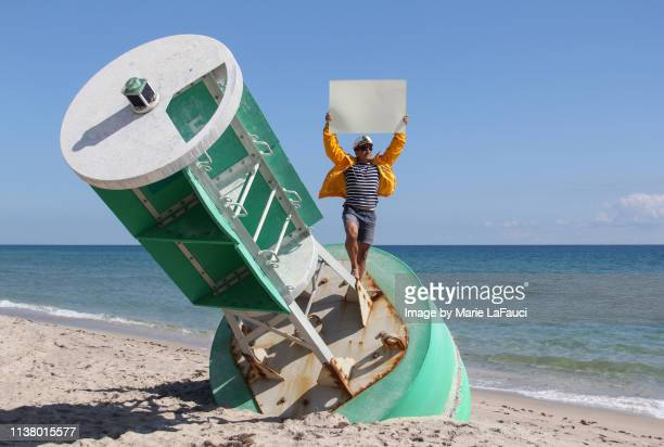 boat captain holding a blank sign while standing on a large buoy - marie lafauci stock pictures, royalty-free photos & images