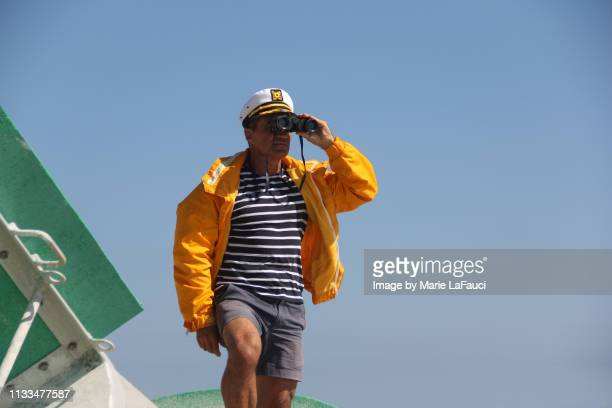 boat captain looking through binoculars - team captain stock pictures, royalty-free photos & images