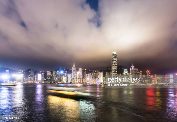 a boat, captured with blurred motion, is crossing the victoria harbor in hong kong - didier marti stock photos and pictures