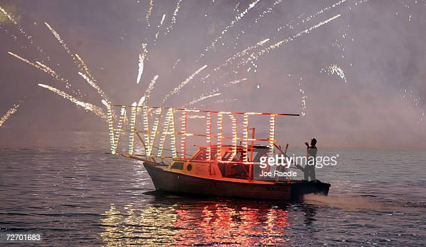 A boat carries a sign spelling out Viva Fidel as fireworks explode over el Morro at midnight in honor of Cuba's President Fidel Castro and to mark...