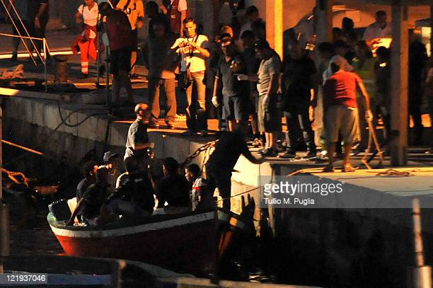 A boat carring migrants arrives in the port of the Italian island of Lampedusa on August 23 2011 in Lampedusa Italy Hundreds of refugees continue to...