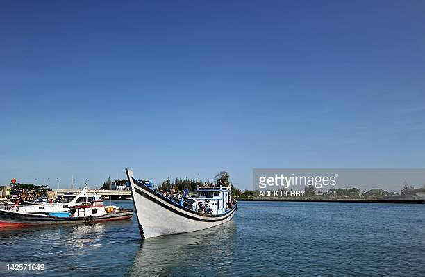 A boat carrying ballot boxes heads to Weh Island during ballot distribution one day ahead of the province's second election in Banda Aceh on April 8...