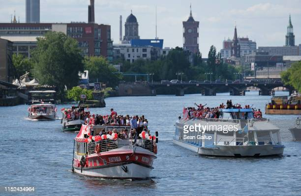A boat carrying members of FC Union followed by other boats carrying fans makes its way along the Spree River during celebrations for the club's...