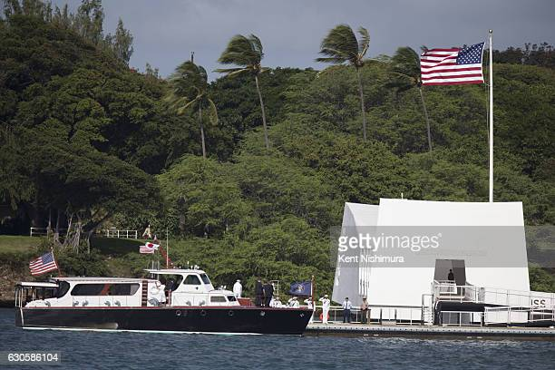 A boat carrying US President Barack Obama and Japanese Prime Minister Shinzo Abe goes by the USS Arizona Memorial at Joint Base Pearl Harbor Hickam...