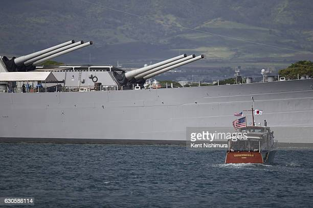 A boat carrying US President Barack Obama and Japanese Prime Minister Shinzo Abe goes by the USS Missouri at Joint Base Pearl Harbor Hickam on...