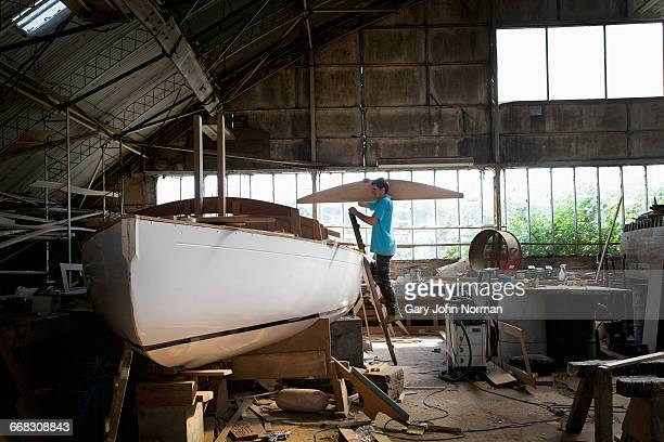Boat craftsman working on boat in workshop