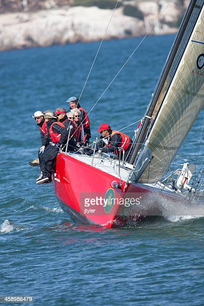 Boat Crew Balancing Their Sailboat While Tacking