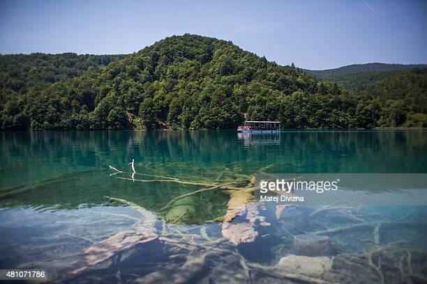 A boat crosses Kozjak lake at Plitvice Lakes National Park on July 6 2015 near Plitvicka Jezera Croatia Plitvice Lakes National Park is Croatia's...
