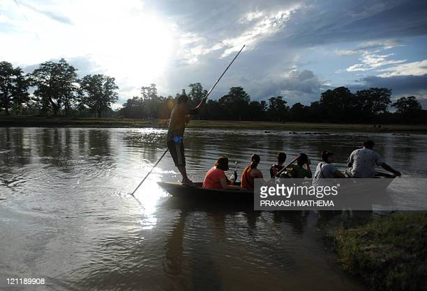 Boat crosses the Rapati river with tourists onboard in Chitwan National Park, around 200 kilometres southwest of Kathmandu on August 15, 2011. The...