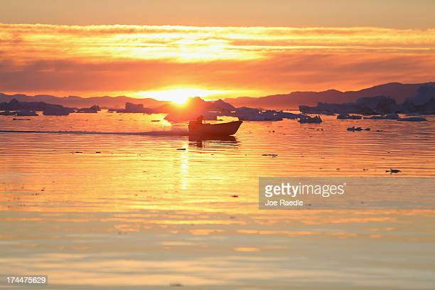 Boat cruises past icebergs that broke off from the Jakobshavn Glacier as the sun reaches its lowest point of the day on July 23, 2013 in Ilulissat,...