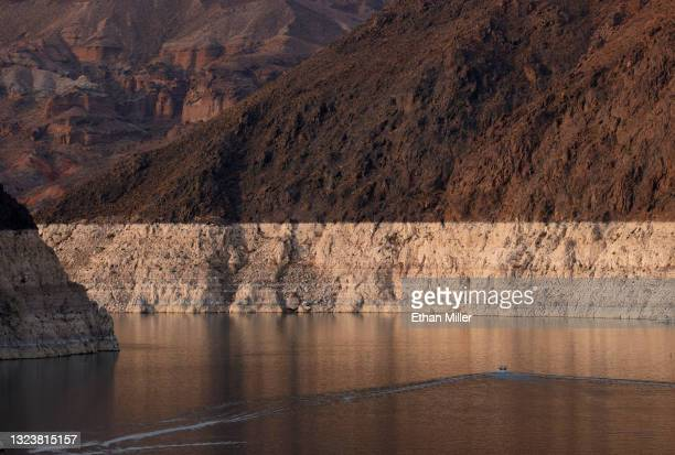 Boat cruises past mineral-stained rocks on the upstream side of the Hoover Dam on June 15, 2021 in the Lake Mead National Recreation Area, Nevada....