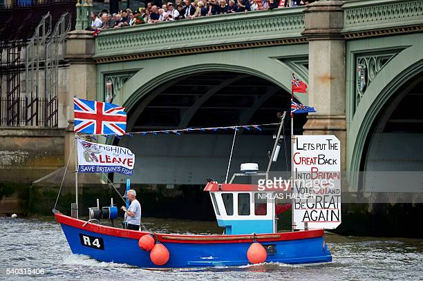 A boat decorated with flags and banners from the 'Fishing for Leave' group campaigning for a 'leave' vote in the EU referendum sail under Westminster...