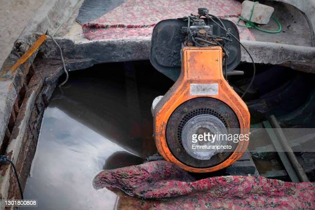 boat engine in a wooden boat filled with rainwater. - emreturanphoto stock pictures, royalty-free photos & images