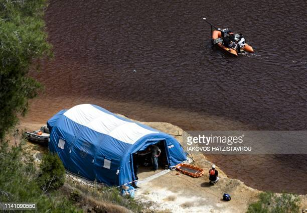 A boat equipped with a sonar system sails on the acidic Red Lake near the village of Mitsero southwest of the capital Nicosia during the search for...