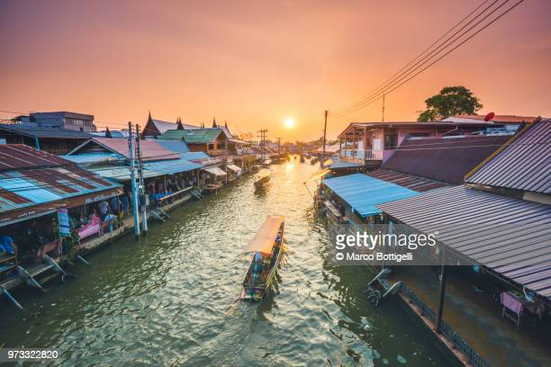 boat floating along amphawa riverside market, bangkok, thailand. - bangkok fotografías e imágenes de stock