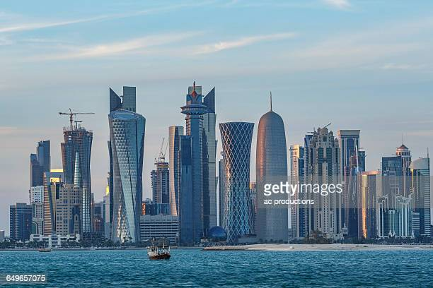 boat floating near doha skyline, doha, qatar - doha stock photos and pictures