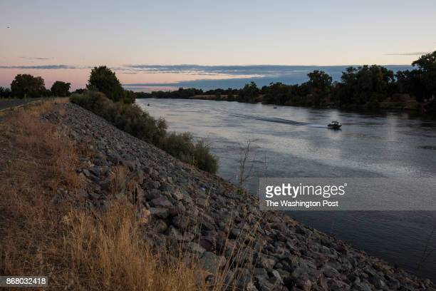 Boat floats down the Sacramento River, next to a levee that stops the river from flooding neighborhoods in West Sacramento, near the construction...