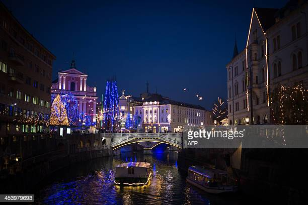 A boat floats on the Ljubljanica river in the centre of Ljubljana as it is illuminated with Christmas decorations on December 6 2013 AFP PHOTO / Jure...