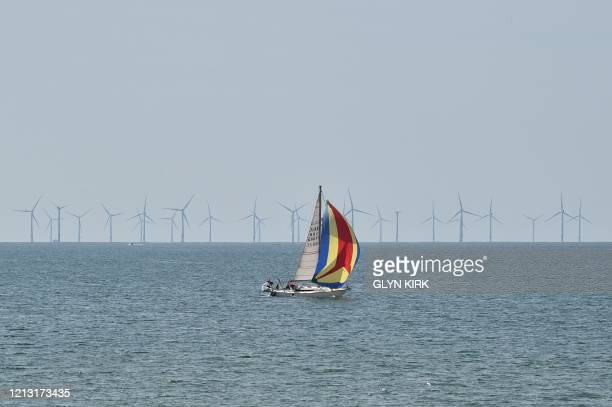 A boat floats on the water in front of offshore wind turbines off the coast of Brighton southern England on May 16 following an easing of lockdown...