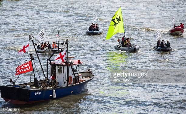 A boat from the 'Fishing for Leave' campaign group and smaller boats from the 'In' campaign join a flotilla along the Thames River on June 15 2016 in...