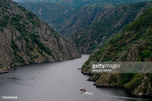A boat goes across the Sil river near the village of Sober in the Galicia region of northwestern Spain on July 21 2018 The Sil Canyon located in the...