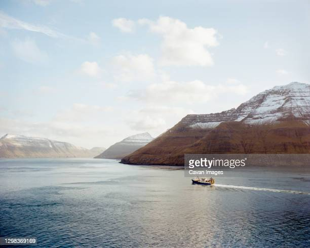 boat going between two mountains in the faroe islands - north stock pictures, royalty-free photos & images