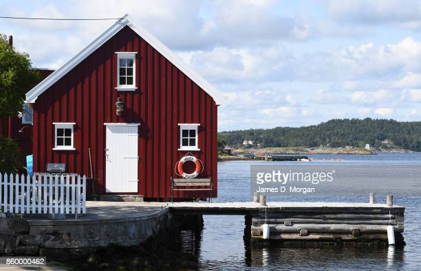 Boat house resting on the edge of Sogne harbour in Southern Norway in Norway in August 22nd 2017