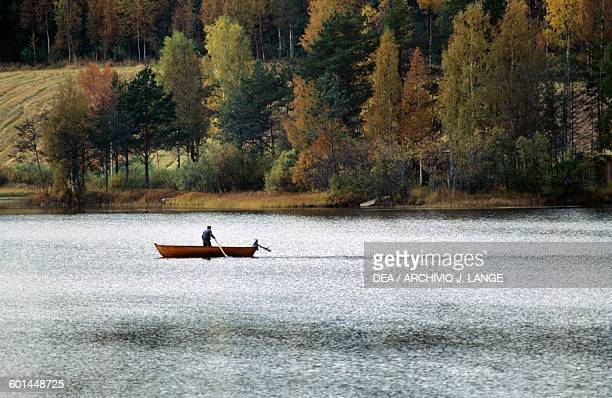 A boat in a lake with trees in the background Lakeland Finland