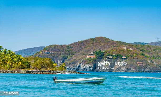 boat in calm waters with homes and town in the background - ixtapa zihuatanejo fotografías e imágenes de stock