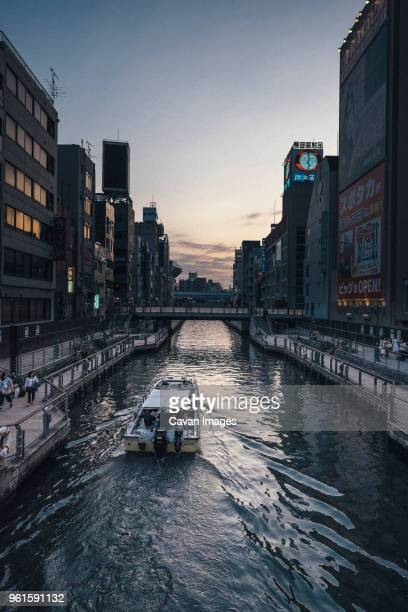boat in dotonbori canal amidst buildings in city - 道頓堀 ストックフォトと画像