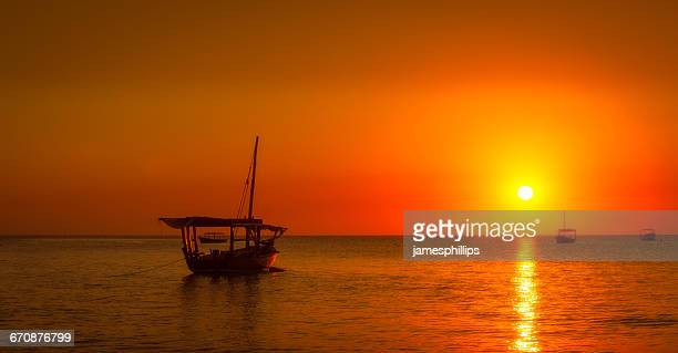 boat in ocean at sunset, zanzibar, tanzania - zanzibar island stock photos and pictures