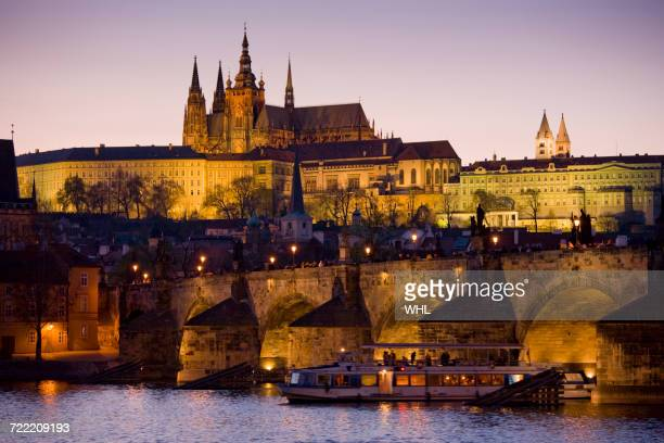 boat in river at night in prague, czech republic - vltava river stock photos and pictures