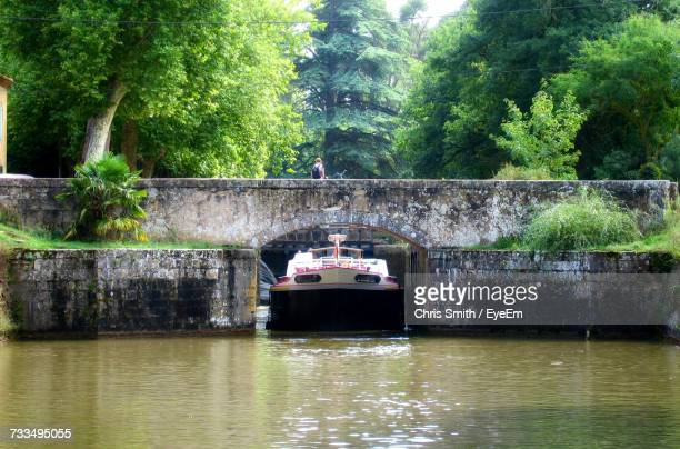 boat in river by trees in forest - canal du midi photos et images de collection