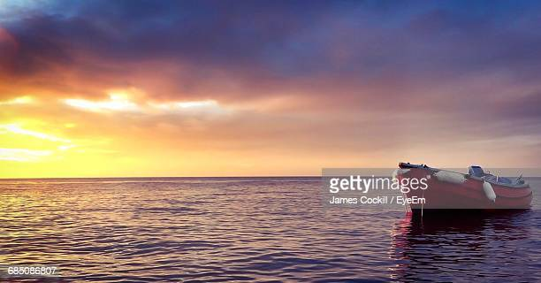 Boat In Sea Against Cloudy Sky During Sunset