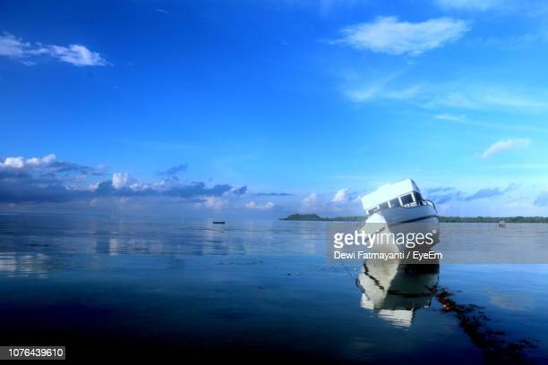 boat in sea against sky - dewi fatmayanti stock photos and pictures