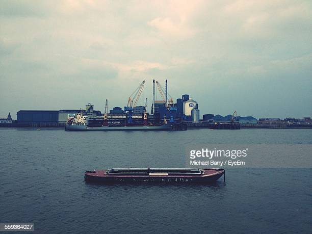 Boat In Sea With Commercial Dock In Background Against Cloudy Sky
