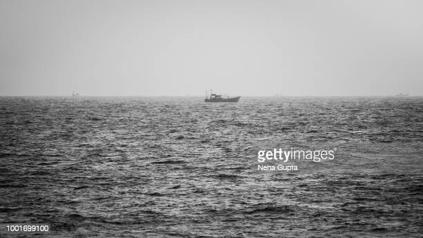 boat in the middle of the ocean - monochrome - mid section stock photos and pictures