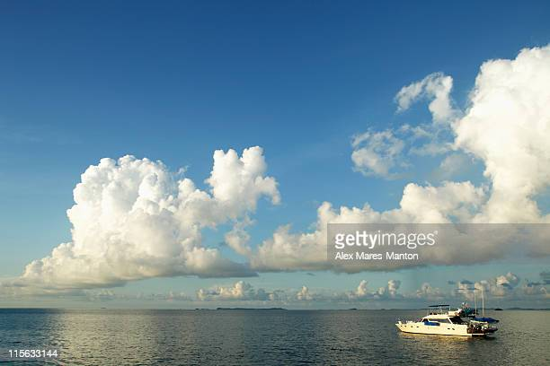 boat in the ocean with clouds and blue sky as background - as stock pictures, royalty-free photos & images