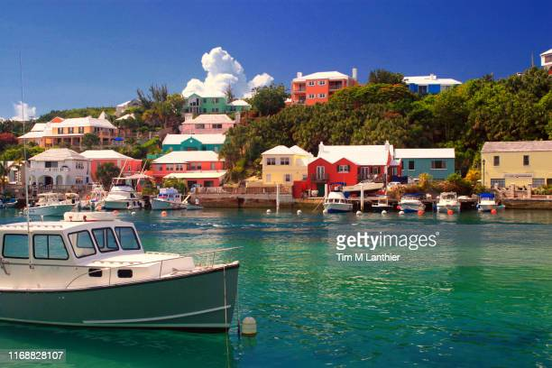 boat in tropical water with colorful houses in background - bermuda stock pictures, royalty-free photos & images