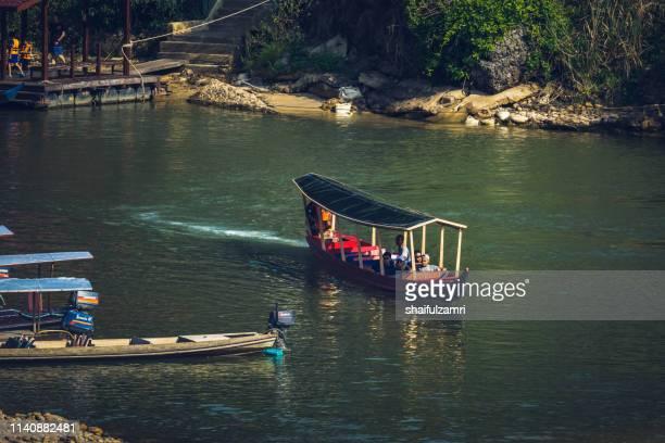 boat is a main transportation in tropical rain forest landscape at taman negara, pahang, malaysia. - shaifulzamri stock-fotos und bilder