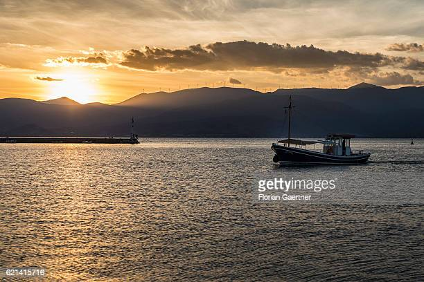 A boat is captured in front of the sunset on November 05 2016 in Nafplio Greece