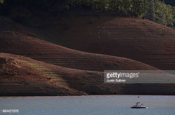 A boat is dwarfed by the steep banks of Shasta Lake on August 30 2014 in Redding California As the severe drought in California continues for a third...