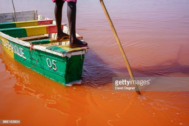 Boat is pushed through the water of Lac Rose on the edge of Dakar, Senegal. Lac Rose is a saline lake that gets its color from a special type of...