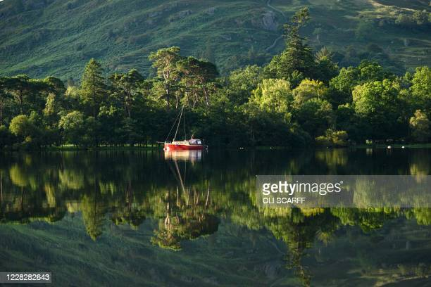 Boat is reflected in the early morning sunshine on Ullswater near Glenridding in the Lake District in north west England on Bank Holiday Monday,...